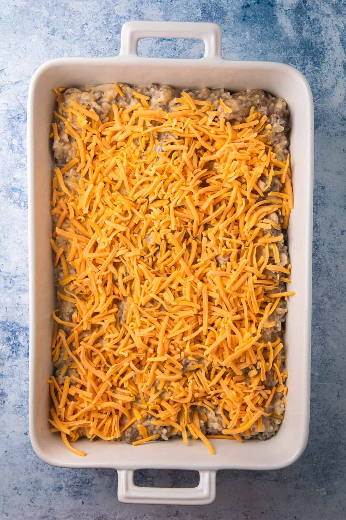 a casserole dish filled with a ground beef and rice mixture and cheese topping