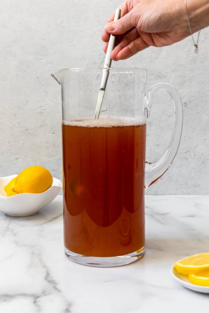 mixing brewed tea and lemonade in a glass pitcher