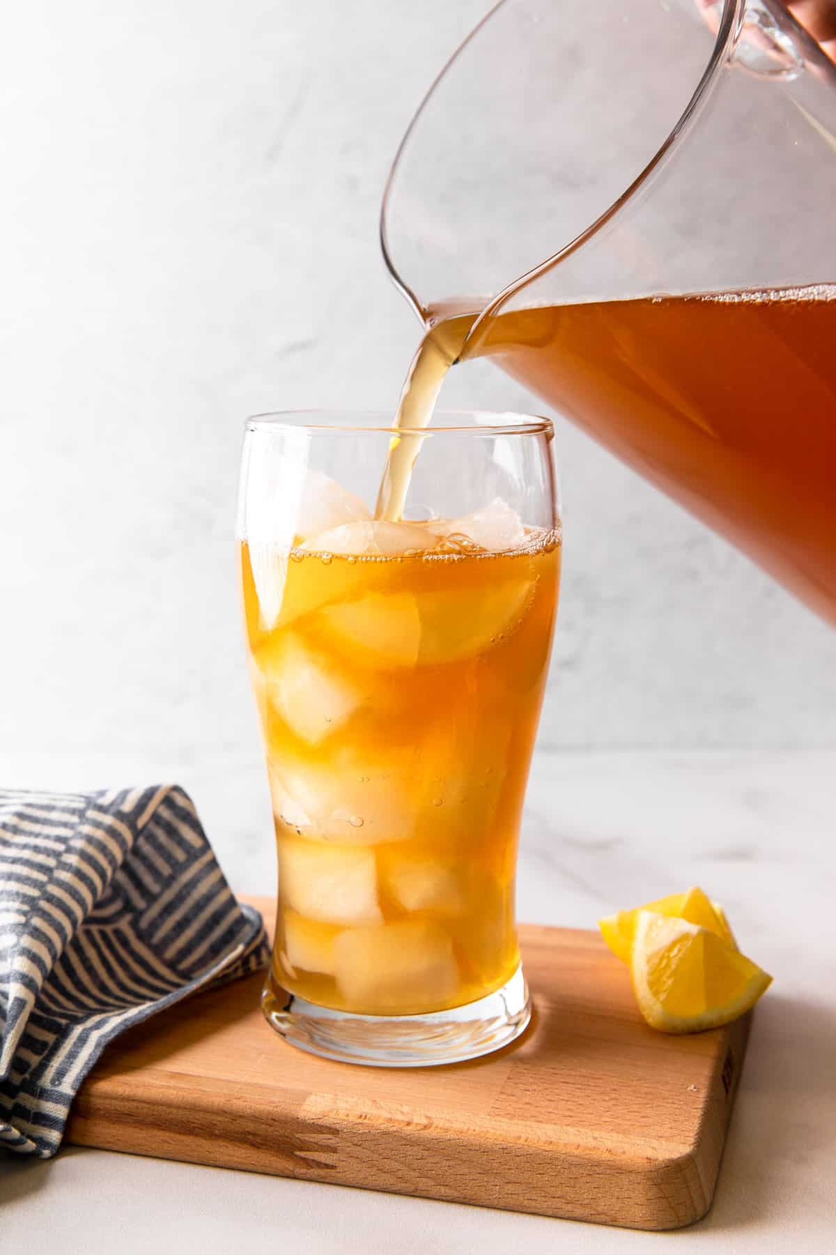 pouring iced tea lemonade mixture into a glass filled with ice