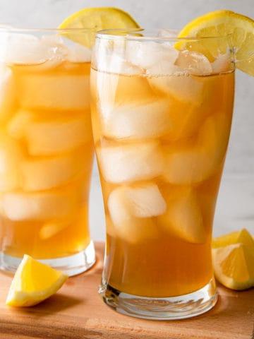 two glasses of iced tea lemonade with lemon wedges
