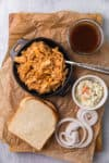 shredded bbq chicken in pan with fixins on the side