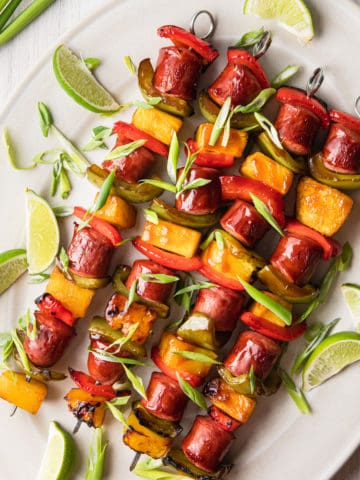 sausage kabobs on a platter with green onions and limes
