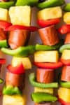 green and red peppers with pineapple and sausage on a skewer.