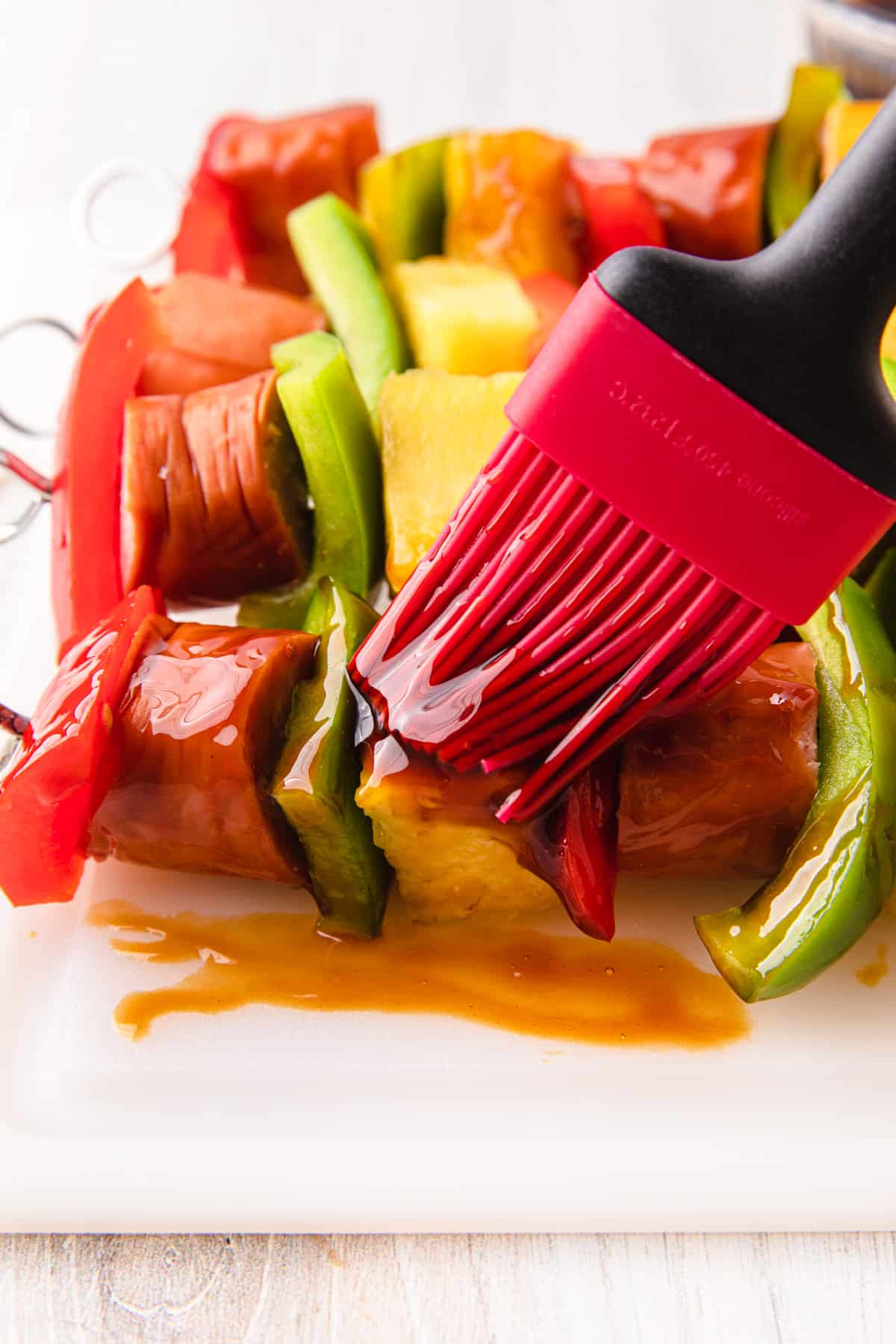 sausage and vegetables threaded on a wooden skewer while brushed with teriyaki sauce