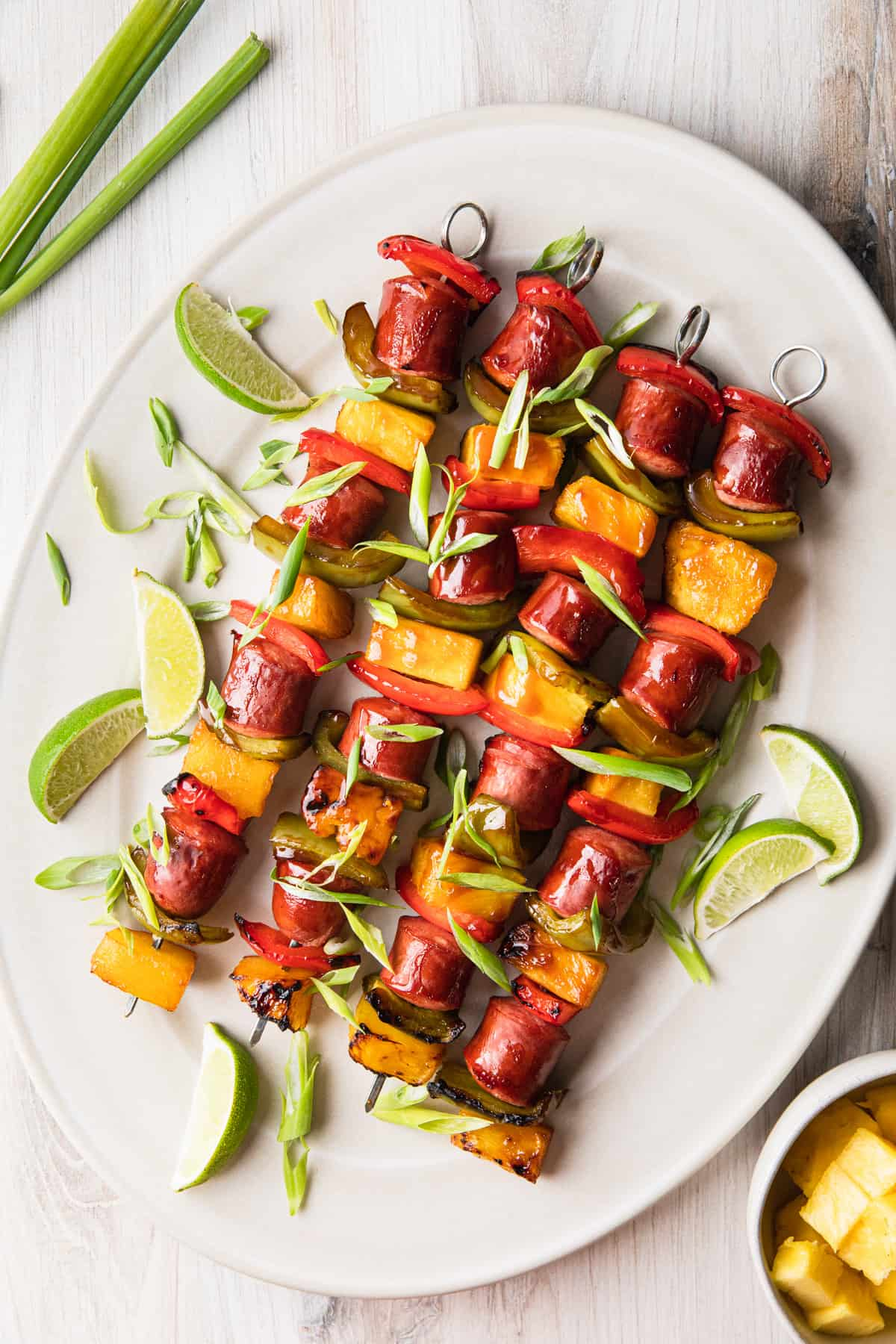 a platter of kabobs with green onions scattered