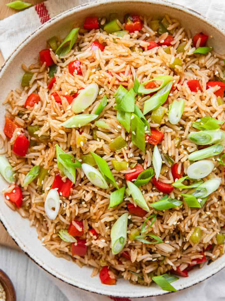 singapore fried rice in bowls with green onion garnishes