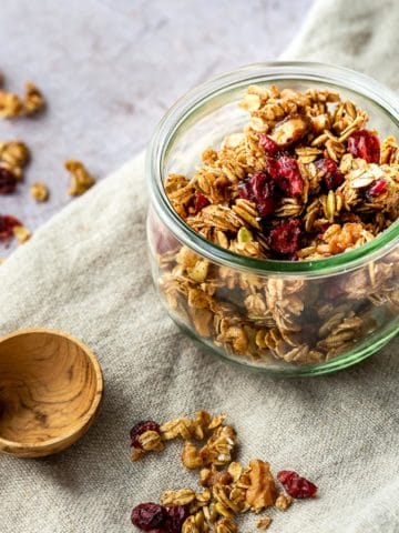 a jar of granola on a cloth with a wooden spoon on the side.