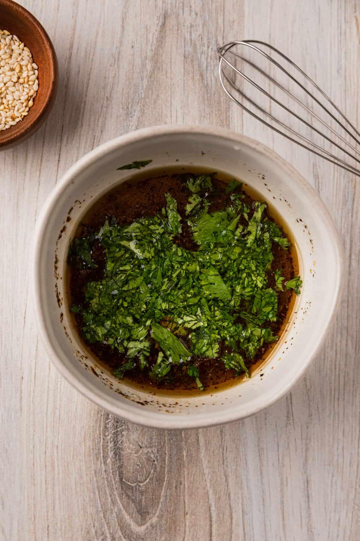 a bowl of vinaigrette with chopped cilantro.
