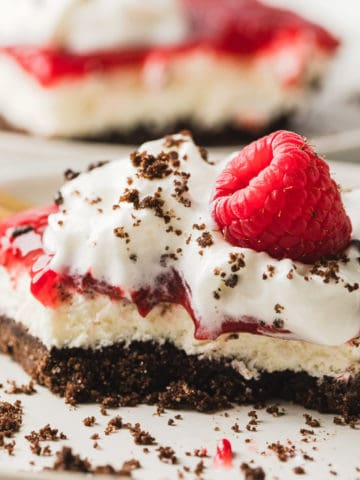 Chocolate Raspberry Dessert Bars on a white plate and topped with a fresh rapsberry.
