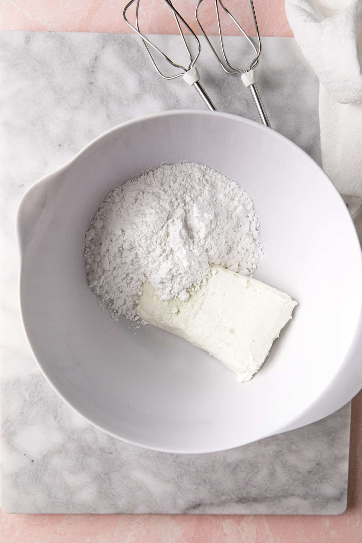 Cream cheese and powdered sugar in a bowl.