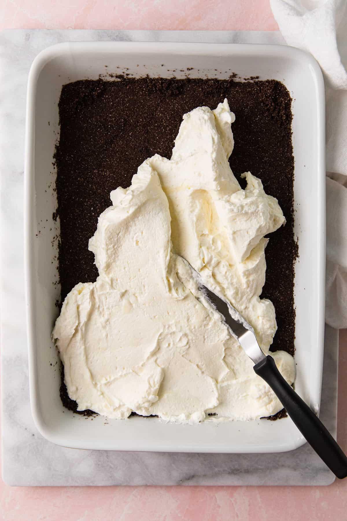 Spreading cream cheese mixture over chocolate crust.