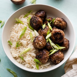 A bowl of meatballs over rice with green onion garnishes.