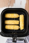 uncooked corn on the cob in an air fryer basket