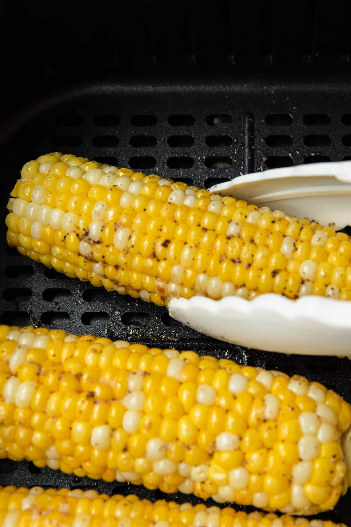 turning corn over with tongs