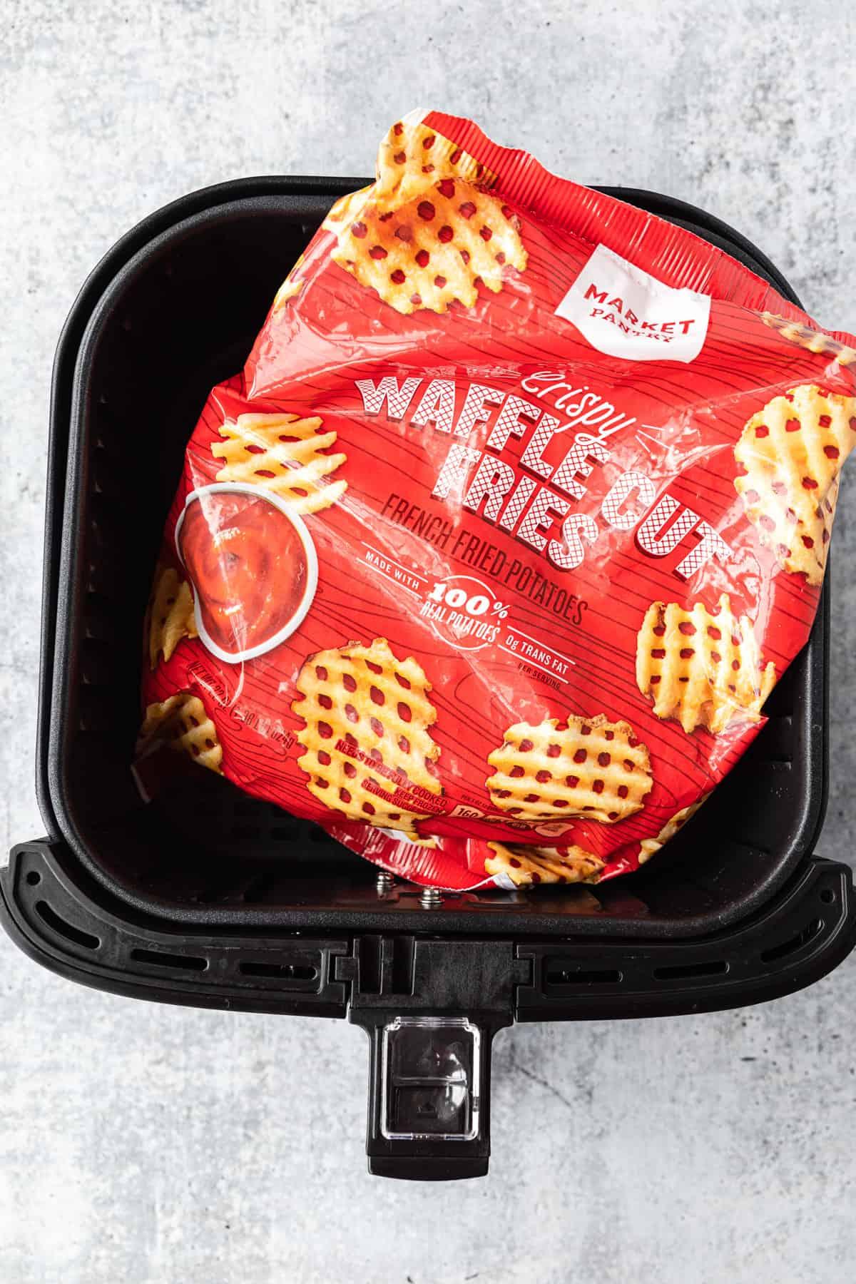 a bag of frozen waffle fries in an air fryer basket