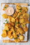 waffle fries on a cutting board with parchment paper and a pink dipping sauce