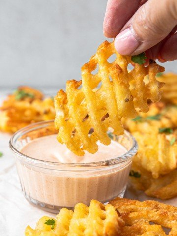 dipping a waffle fry into a pink sauce