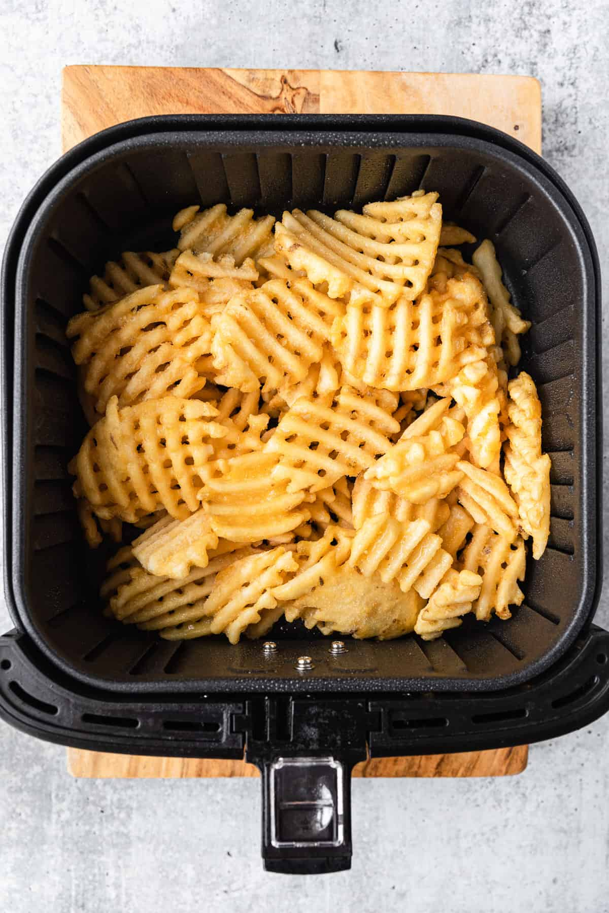 frozen waffle fries in the basket of an air fryer