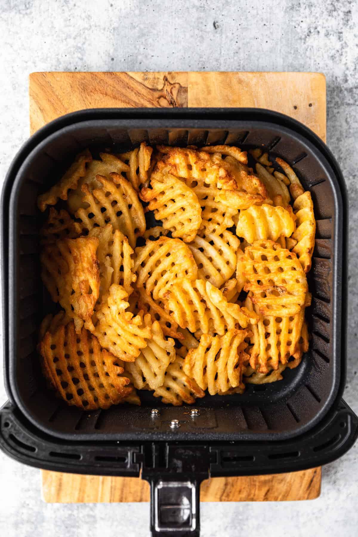 golden brown waffle fries in an air fryer basket