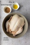 a raw whole chicken with some olive oil and seasoning off to the side