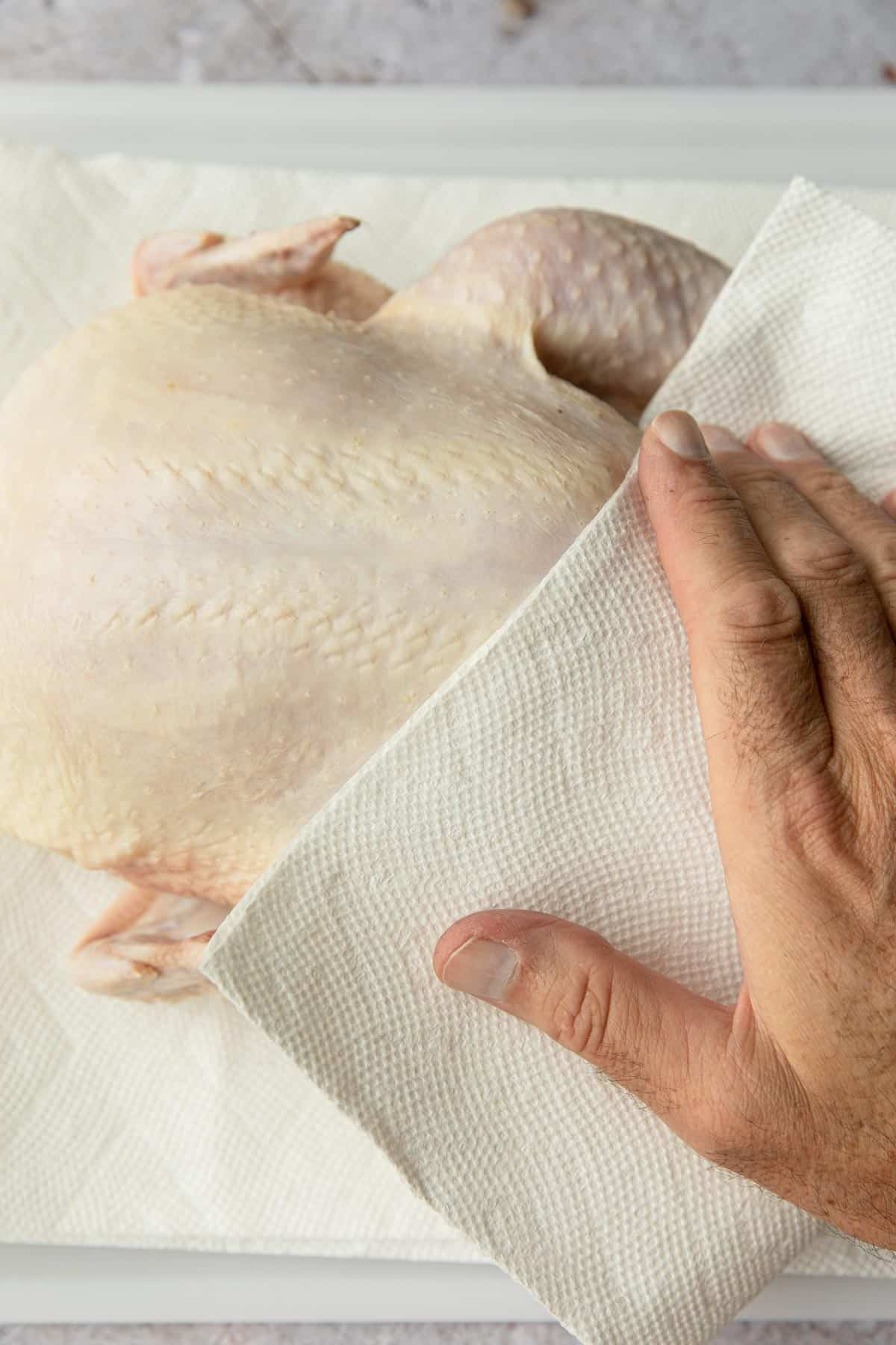 patting a raw chicken dry with paper towels
