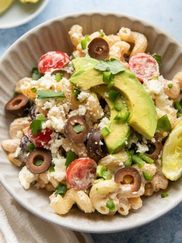 a bowl of corn and black bean pasta salad with lime wedges