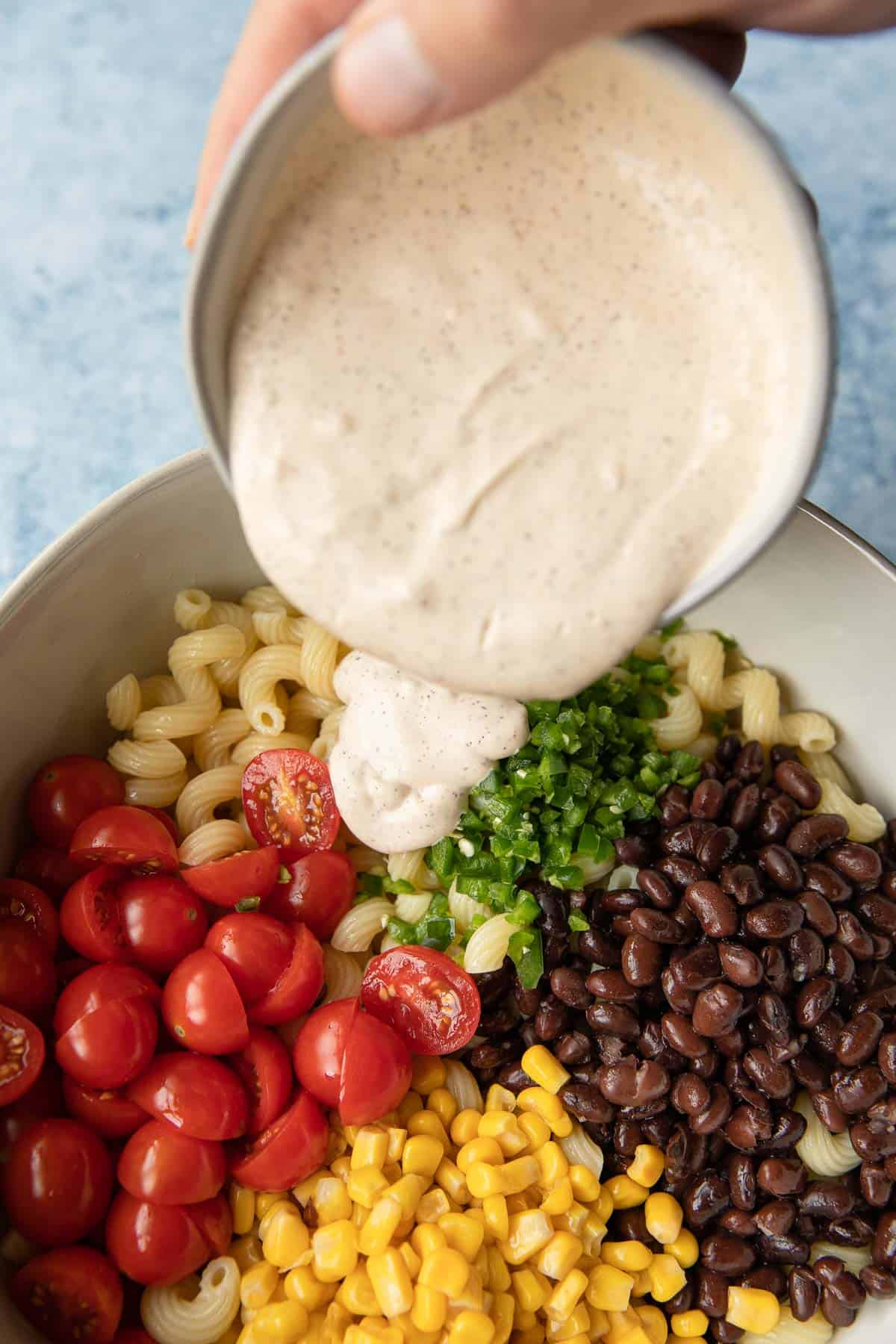 pouring a creamy dressing into a pasta salad bowl