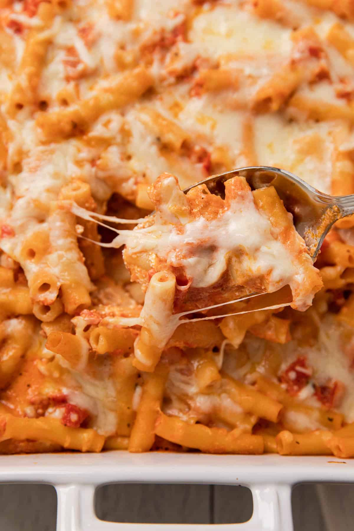 a casserole dish with a cheesy pasta dish being scooped out