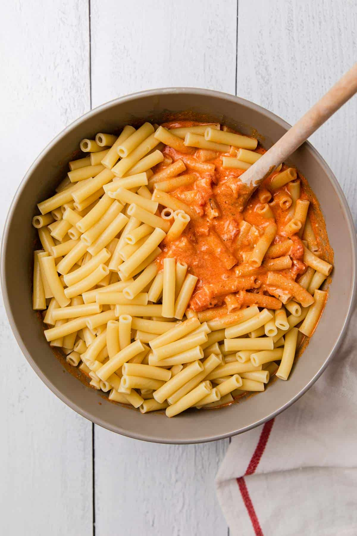 a bowl of sauce and ziti before mixing