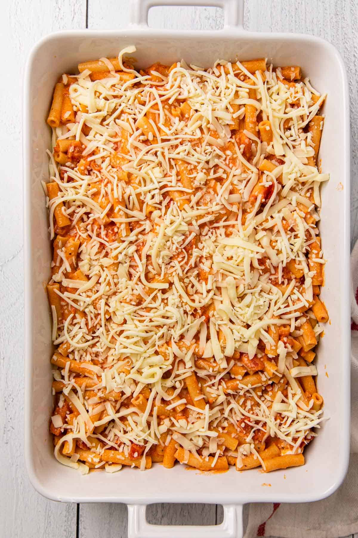 a casserole dish being layered with pasta, sauce, and cheese