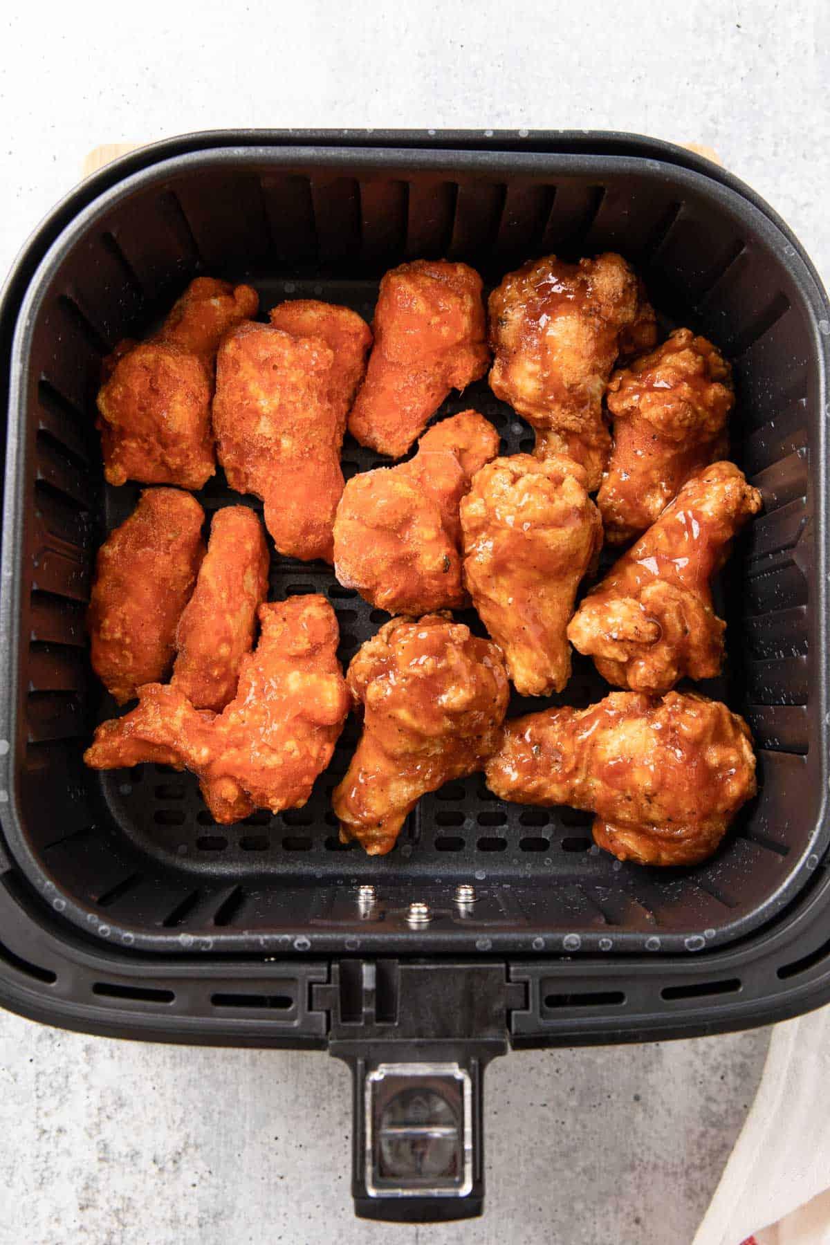 frozen preseasoned chicken wings in an air fryer baskt