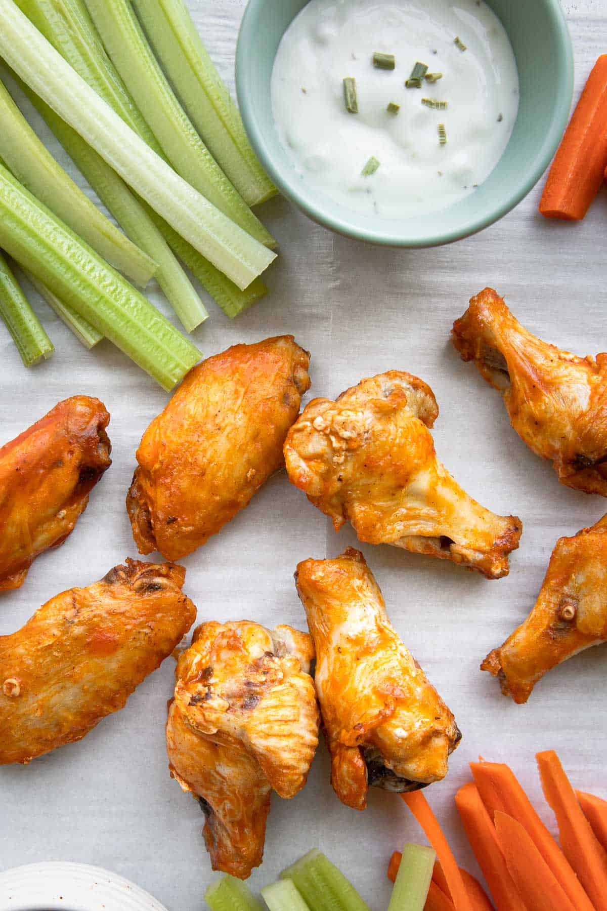 wing on a parchement paper with celery sticks, carrot sticks, and dip